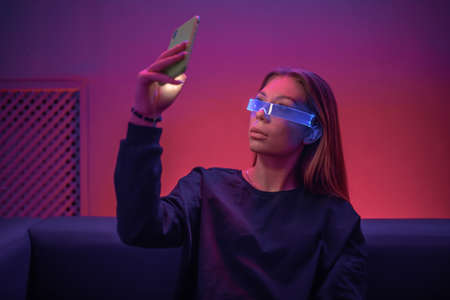 Young woman in glowing glasses uses the phone Standard-Bild - 160818065