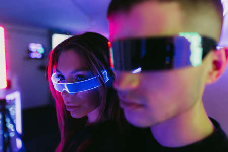 A couple of people standing under a neon light. Futuristic glasses. Standard-Bild