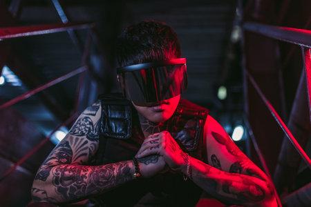 Cyberpunk style. Tattooed guy in one city. Cyber glasses. Standard-Bild