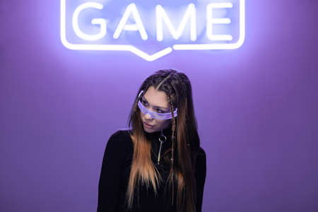 Woman in neon glasses in a neon room with neon game signs Standard-Bild - 161017124