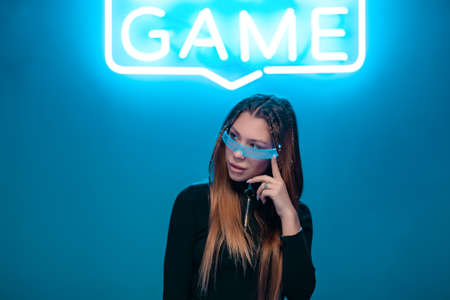 Cool stylish girl with a fashionable hairstyle and stylish glasses with a large glass poses on a bright neon background. Standard-Bild - 161017129