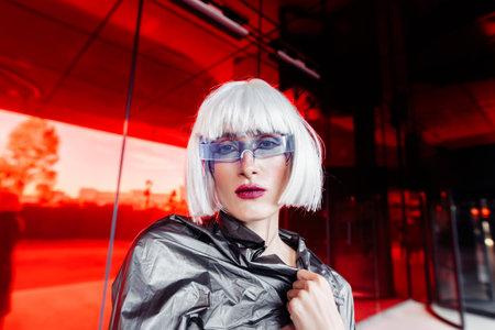 Fashion portrait of a blonde on a red background. Standard-Bild