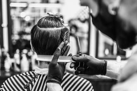 Barber makes a haircut and hair styling in a barbershop, beauty salon.