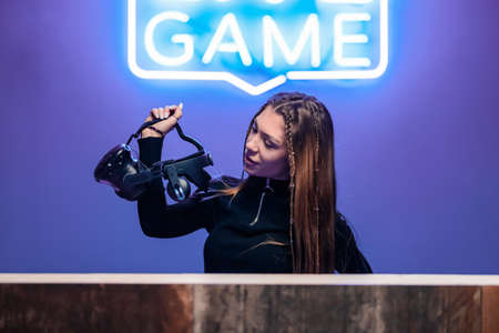 Young woman holding VR glasses.