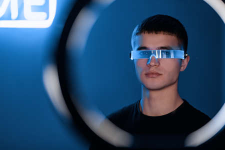 Portrait of a young man with neon cyber glasses. Standard-Bild