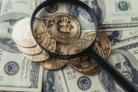 Magnifying glass, bitcoins in dollars.
