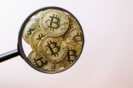 Bitcoin under a magnifying glass on a pink background. There is room for text. Standard-Bild