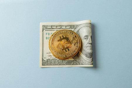 Bitcoin on dollar on a blue background.