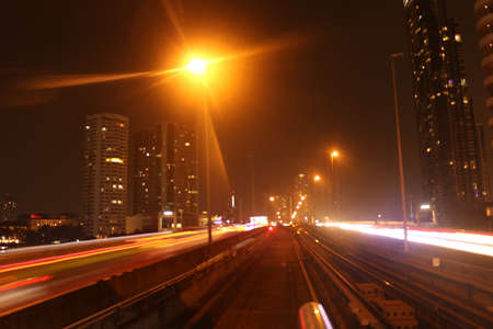 Bangkok City on February 22, 2020 at 11:06 pm: view from the driver's seat from a skytrain on the tracks in front with lightening effects at night with corporate buildings in background Editoriali