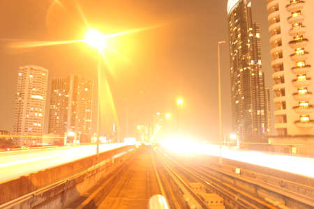 Bangkok City on February 22, 2020 at 11:06 pm: view from the driver's seat from a skytrain on the tracks in front with lightening effects at night with corporate buildings in background