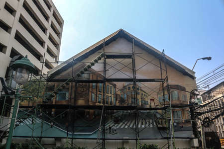 Bangkok City on February 21. 2020 at 03:52 pm: old house wall getting a nice painting with urban life, buildings and transportation. Still with scaffolding. Publikacyjne