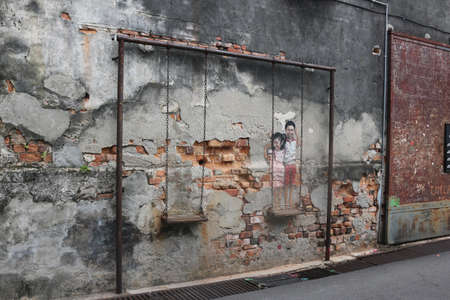 Street art Boy and Girl on a Swing by Louis Gan Yee Loong NOT Ernest Zacharevic, Georgetown, Penang, Malaysia on February 2, 2020