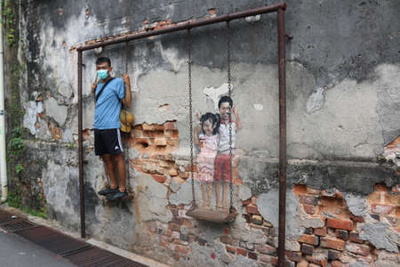 Asian man standing.Street art Boy and Girl on a Swing by Louis Gan Yee Loong NOT Ernest Zacharevic, Georgetown, Malaysia on February 2, 2020