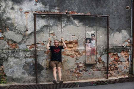 Caucasian man sitting. Street art Boy and Girl on a Swing by Louis Gan Yee Loong NOT Ernest Zacharevic, Georgetown, Malaysia on February 2, 2020 新闻类图片