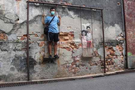 Asian man standing.Street art ´Boy and Girl on a Swing´ by Louis Gan Yee Loong not E Zacharevic, Georgetown, Penang, Malaysia on February 2, 2020