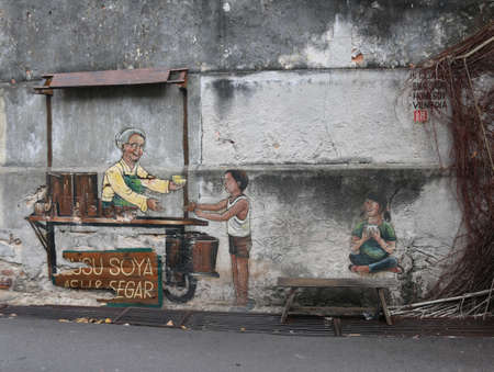 Street art mural called ´Old lady selling Susu Soya Asli & Segar´ in Georgetown, Malaysia on February 2, 2020. Boy buying, sitting girl on bench