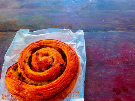 High angle view from one brioche raisin snail bun roll with cinnamon from a french or danish pastry backery in spiral shape.