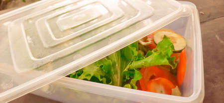 Green lettuce salat leaves, tomato and cut cucumber in an open food storage container. Standard-Bild