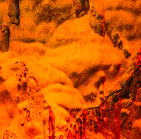 Smooth abstract shapes from gnomes or trolls on yellow red flowing stone cave wall, which looks like cave painting.