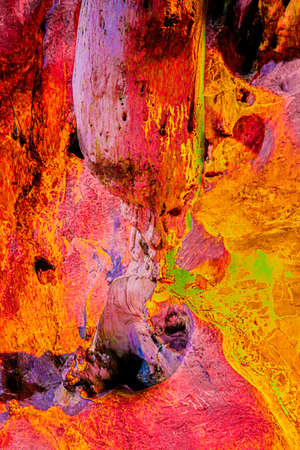 A gnome below a stalactite. An imagination which comes from a closeup from a flowing stone. These abstract shapes on a dripstone are on a cave wall.