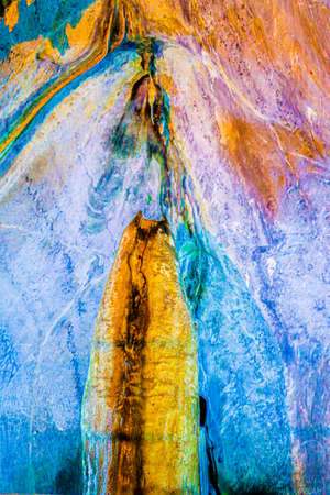 Devil meets two angels in heaven. Abstract art made by nature. Dripstone closeup in a cave. Fantasy backdrop in multi colors with sacral mood. Standard-Bild