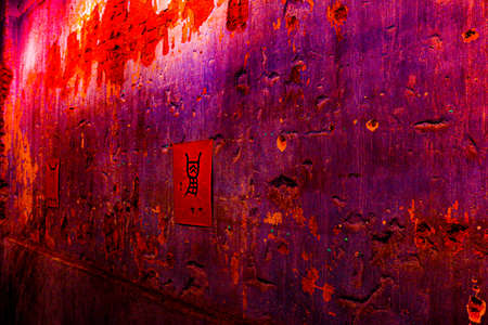 Small red poster with Chinese script hanging on a wall in vintage style, damaged, with bright grey cement and bricks. Standard-Bild