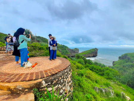 Young adult local tourist enjoying their trip to a rocky beach in Gunung Kidul area on Java, Indonesia on Sylvester afternoon, December 31, 2020