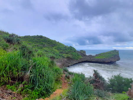 High angle view from a rocky lagoon beach with a cliff in Gunung Kidul Standard-Bild