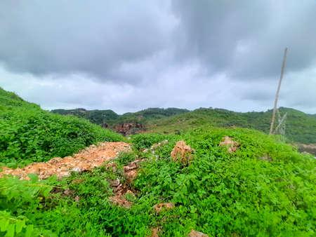 A small trail through green rocks close to a beach in Gunung Kidul area Standard-Bild
