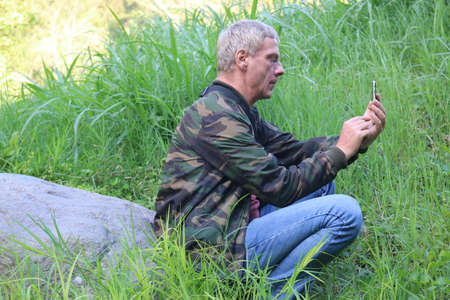 Profile view from a Caucasian mature adult man, using his smartphone, while sitting on a stone in a meadow. Low angle view. Standard-Bild
