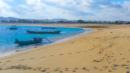 Beautiful paradise lagoon beach background with white sand, blue water and clear sky and a small longtail boats at Tanjung An on Lombok in Indonesia. Standard-Bild