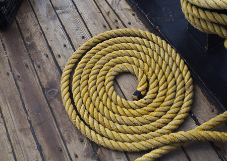 Background texture of coiled marine or nautical rope on wooden deck