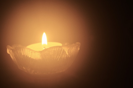 One tealight with a tiny flame against black background Stock Photo