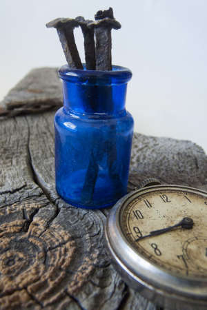 knothole: Weathered wood background with antique blue bottle, nails and pocket watch