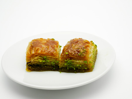 ottoman empire: two baklava, sweet pastry made of layers of filo filled with pistachio and held together with syrop. Ottoman Empire cuisine. Stock Photo