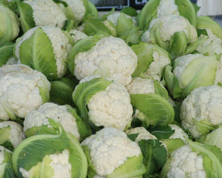 A stack of cauliflower heads for sale at an outdoor market Stock Photo - 910468
