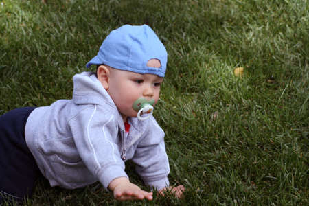Baby, with a pacifier in his mouth, crawling