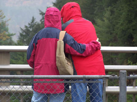 A man and a woman in red jackets, embracing on a bridge