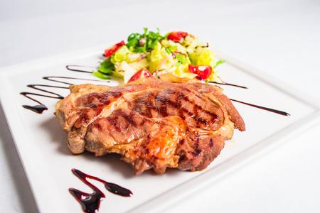 carnes y verduras: cuello de cerdo a la plancha, ensalada de guarnición Foto de archivo