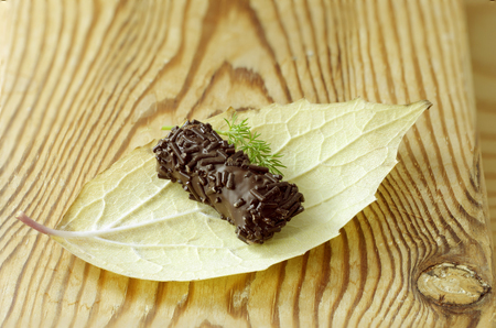 Chocolate candy on autumn leaf, on a wooden counter Stock Photo