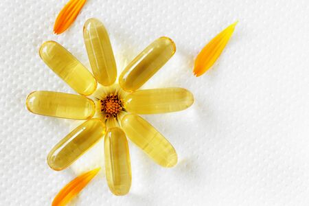 Fish oil capsule, flower, white background 1 Stock Photo