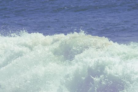 Large blue surfing wave breaks in the ocean Stock Photo