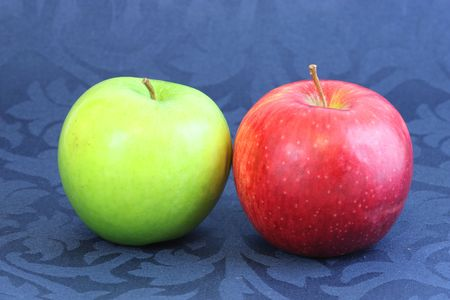 green and red apples on blue background