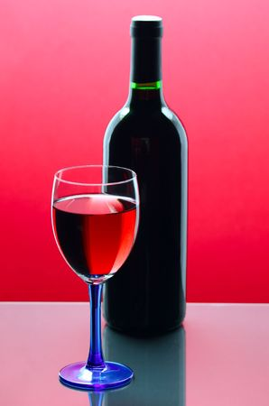 red wine glass with bottle in background Stock Photo