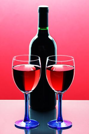 Glasses of red wine  and bottle in background