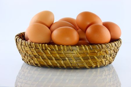 Eggs in wicker basket with white background