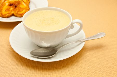 Closeup of coffee with milk in white cup and a palmier pastry Stock Photo