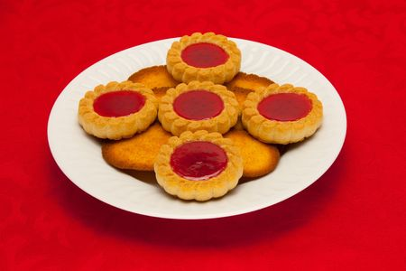 A plate of cookies on red background