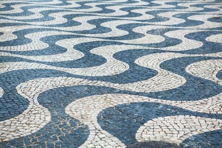 Calcada, typical portuguese sidewalk, made of small stones photo