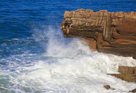 Marine wave breaks against offshore stone
